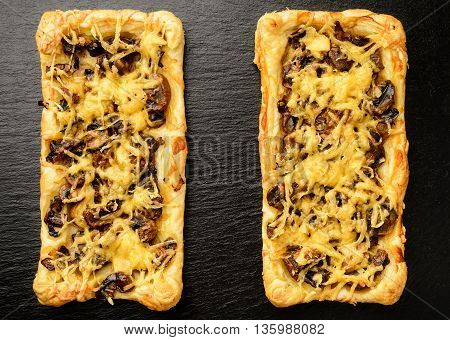 Puff pastries with mushrooms and cheese on black background.