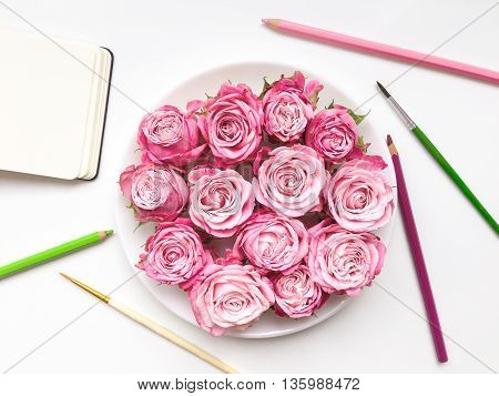 Colorful composition with roses sketchbook and accessories. Flat lay on white table top view