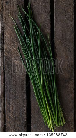 Fresh green chives on wooden board