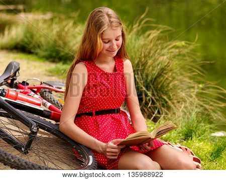 Bikes cycling girl. Girl wearing red polka dots dress rides bicycle into park. Girl read book. Girl sits leaning on bicycle on shore
