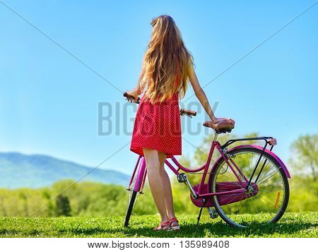 Bikes bicycle girl. Teenager girl wearing red polka dots dress looking into distance keeps bicycle with flowers basket. Green grass. Back view.