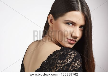Beautiful woman with long brown hair posing for photographer in studio ober white background. Modern hairstyle concept in studio.
