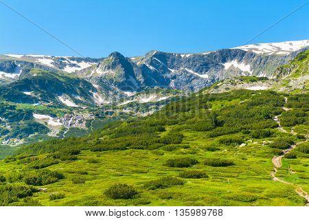 Spring green foliage and snow Rila Mountains by Rila Lakes in Bulgaria