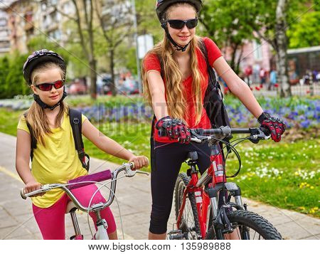Bikes bicyclist girl. Girls wearing bicycle helmet with rucksack ciclyng bicycle. Girls children cycling on yellow bike lane. Bike share program save money and time.