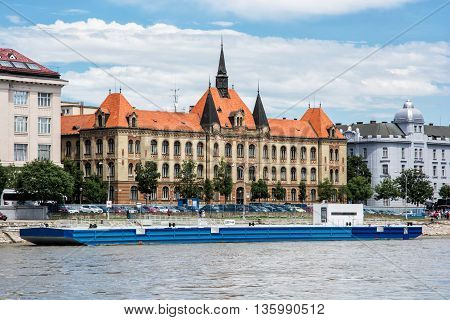 Waterfront of the Danube river in Bratislava Slovak republic. Beautiful architecture and cargo ship. Building of the secondary technical school. Flowing water in the river.