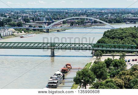 Bridges over the Danube river in Bratislava city Slovak republic. Old bridge and Apollo bridge. Ship transportation. Capital city of Slovakia. Travel destination.