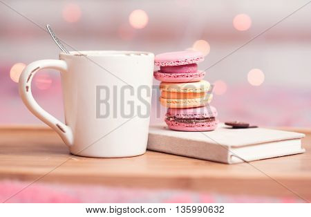 Cup of tea stack of macaroons book staying on wooden tray over christmas lights closeup. Selective focus.