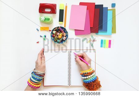 Female hand writing in diary. Colored bracelets scarf turtleneck lemon color blue turquoise white background.