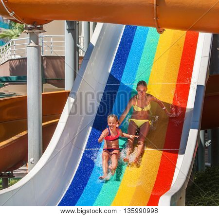 Two children on water slide at aquapark and thumb up. Summer holiday. There are two water slides in aqua park. Outdoor.