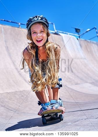 Teen girl skateboarding his skateboard outdoor. Girl in protection for skateboard .