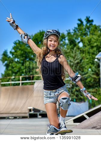 Teen girl rides his skateboard outdoor. Teen in protection for skateboard.