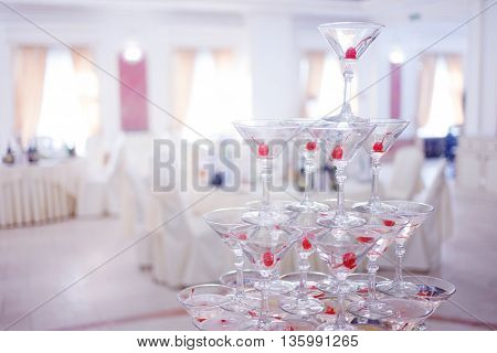 Glass goblets. Pyramid of champagne. The hill of glasses of wine and cherries. Glasses for alcohol. Festive drink. Bartender show. Decorations for the Banquet.