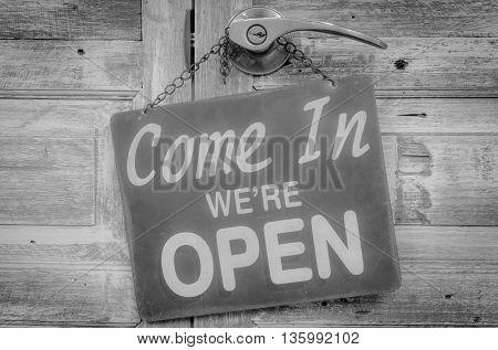 Come In We're Open on the wooden door Black and white Photo.