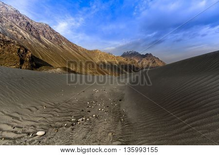 sand dunes against the background of distant colorful mountain range and sunrise sky Ladakh Himalaya Jammu & Kashmir Northern India