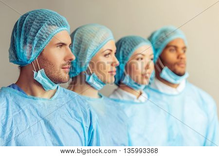 Surgeons of different nationalities and genders in masks and caps are looking forward standing in a row one by one