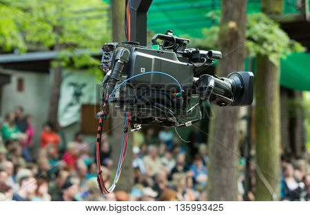 Professional camera on a telescopic arm with blurred background.