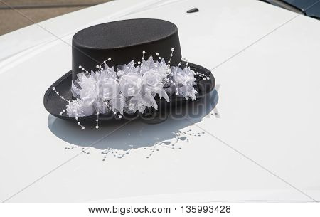Hat with white flowers on the front hood of a white car wedding decorations
