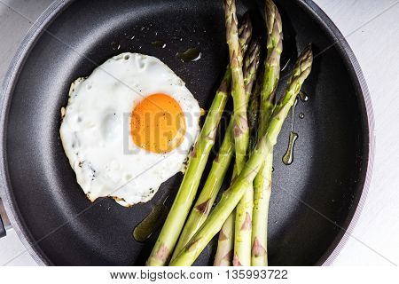 Green asparagus with fried egg on the frying pan