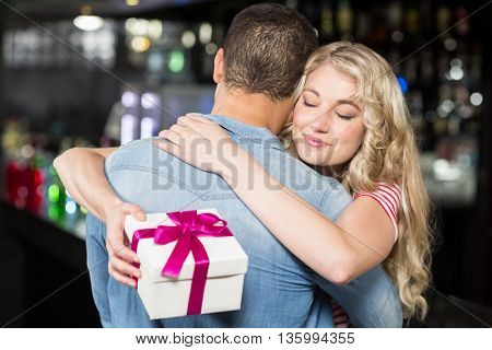 Cute couple hugging having a gift in a pub