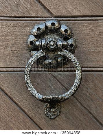 Knocker hammered metal door knocker. The door to the vault in sandstone.