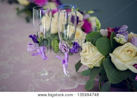 arrangement of different flowers is on the table with glasses of the newlyweds, wedding