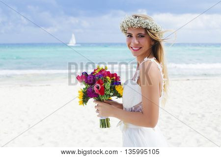 Beautiful bride holding her bouquet, wearing a flower crown, in the Mexican Caribbean.