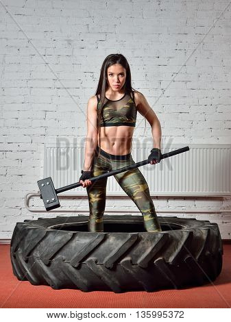 Fit woman with huge hammer posing in gym .