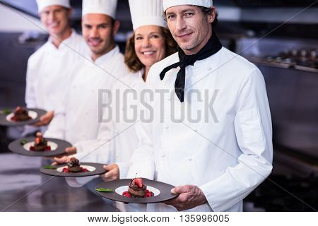 Portrait of happy chefs presenting their dessert plates in the commercial kitchen
