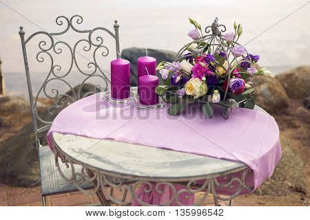 decor design small round table on the nature of the sea with purple lilac tablecloth thick candles and flowers in a cage with roses