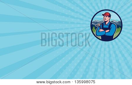 Business card showing illustration of a kitchen bathroom remodeler builder carpenter holding hammer with arms crossed viewed from front set inside circle with mountains in the background done in retro style.