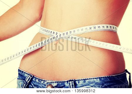 Young woman measuring her waist