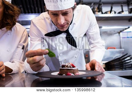 Male chef garnishing his dessert with a mint leaf on counter in commercial kitchen