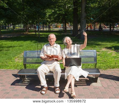 The happy old couple in the summer on a walk in park. The grandfather reading a book. The grandmother with a laptop making selfie