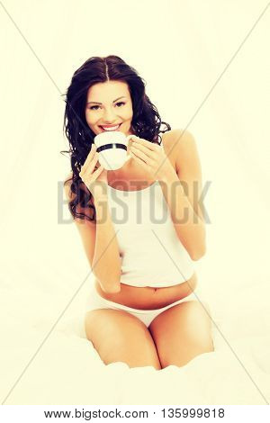 Attractive in bed with mug of something hot.