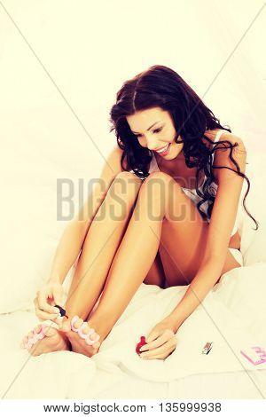 Attractive woman painting her toes.