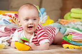 stock photo of babygro  - Happy baby girl with heap of baby - JPG