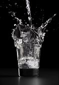 stock photo of water well  - Pouring a glass of water water splashing out of the glass - JPG