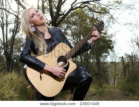 Blonde Lady Playing Guitar And Signing In The Forest