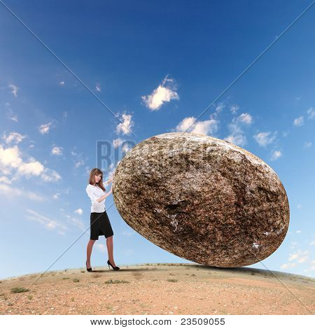 Businesswoman rolling a giant stone