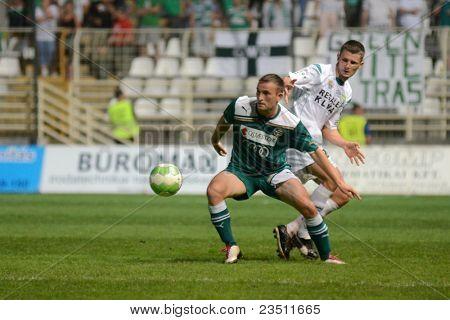 KAPOSVAR, HUNGARY - SEPTEMBER 10: Unidentified players in action at a Hungarian National Championship soccer game - Kaposvar (white) vs Gyor (green) on September 10, 2011 in Kaposvar, Hungary.