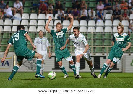 KAPOSVAR, HUNGARY - SEPTEMBER 10: Serghei Alexeev (white 14) in action at a Hungarian National Championship soccer game - Kaposvar (white) vs Gyor (green) on September 10, 2011 in Kaposvar, Hungary.