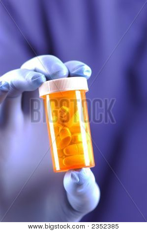 Gloved Hand Holding Pill Bottle