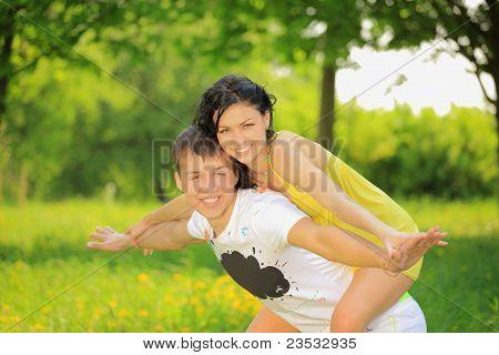 Happy young couple enjoying backriding outdoors