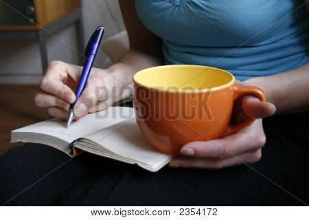 Escritura de mujer en el diario y la taza de café