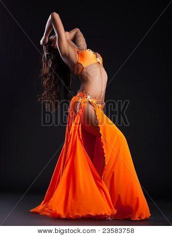 Expressive woman posing in orange arabic costume