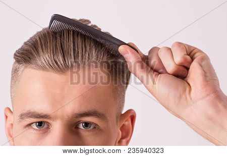 poster of Close up of young attractive man brushing hair with comb in hand, isolated on white background. Man's face with modern and stylish haircut. Male beauty, hair style. Hipster combing hair or making hair