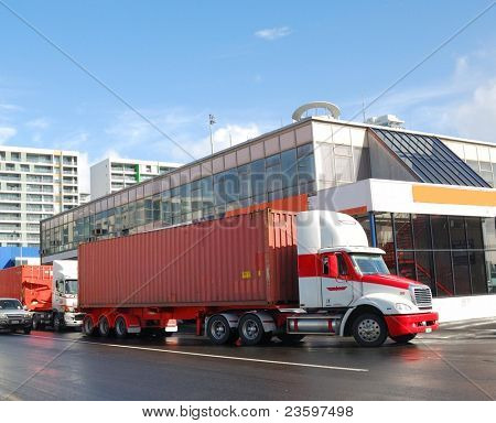 trucks delivering containers into ship yard