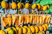 Whole Ripe Yellow Mangoes On Sticks & Sliced Ripe Mangoes In Bags On Street Stall, Guatemala, Centra poster