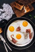 Постер, плакат: Fried Eggs In A Frying Pan With Bacon Toast Napkin Forks Scrambled Egg With Bacon On A Dark Back