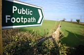 Closeup Of A Public Footpath Sign Taken With A Shallow Depth Of Field, Pointing Across A Green Field poster